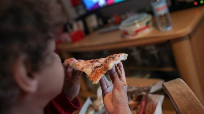 Un niño come un trozo de pizza del menú infantil de Telepizza mientras ve la televisión en su casa, tras recoger el menú en un establecimiento de Telepizza. - Jesús Hellín - Europa Press - Archivo