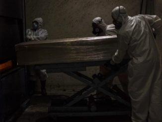 Un grupo de trabajadores con trajes protectores acarrean con el féretro de una persona fallecida a causa de la COVID-19, en Ciudad de México. - Jacky Muniello/dpa